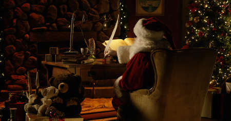 Wide shot of Santa Claus in full Christmas regalia - including cap - sitting in his workshop, looking over the Naughty and Nice List which is written on parchment paper and illuminated by candlelight. He uses a massive quill pen to make adjustments. A cola sits beside him on the table. The room is filled with seasonal decorations.