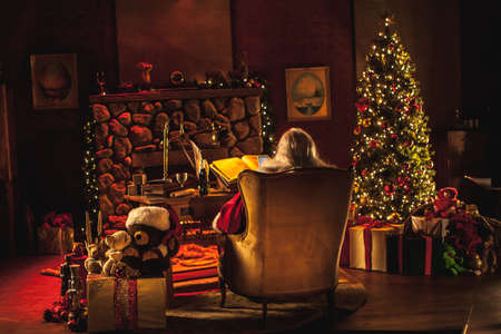 Santa sits at his desk, surrounded by festive Christmas decor and presents Stock Photo