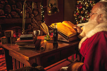 Santa Claus works at his desk using a feather quill