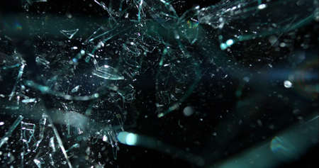 Fractured glass shards hang in the air over a black background after a crash or accident Stock Photo