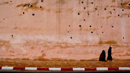full of holes: Walking in the streets of Asilah, Morocco. Wall full of holes Stock Photo