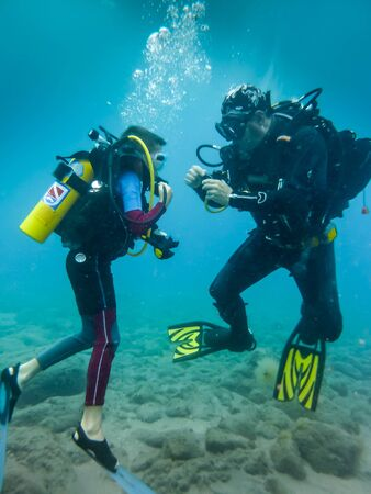 First dive for a child, attentively following the instructions of his father