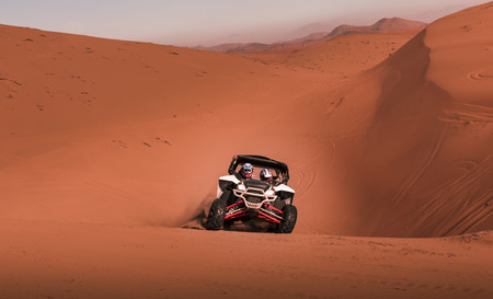 Buggy  in competition, crossing dunes in the desert
