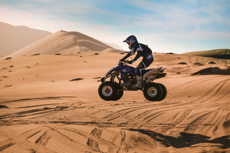 quad: Pilot quad in competition, jumping over the dunes of the Atacama Desert