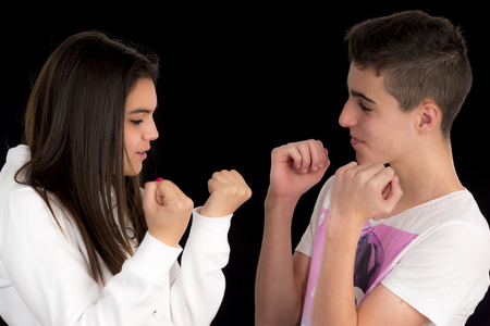 imitating: Teenage couple imitating a fight on a black background