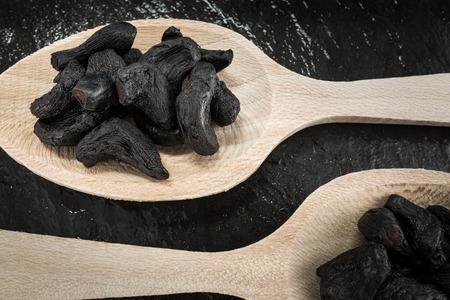 garlic: Dos cucharadas con ajo negro, ingredientes de cocina Foto de archivo