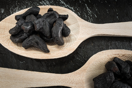 Two tablespoons with black garlic,cooking ingredients Stockfoto