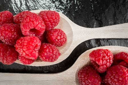 piled: Raspberries piled up on two wooden spoons
