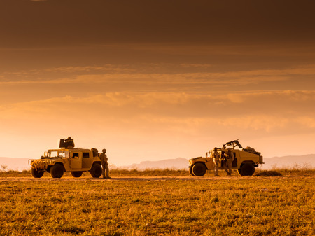 Soldiers marines patrolling on foot and escorted by a Humvee