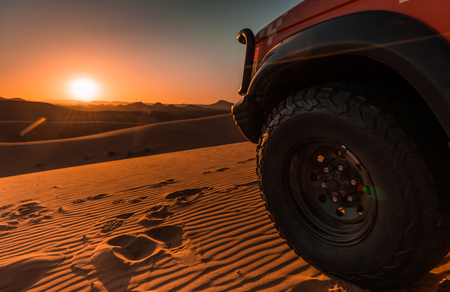 Sunset in the desert with details of a 4x4 vehicle Stockfoto
