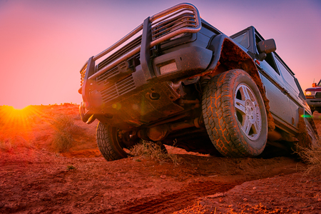All-terrain vehicle raising a wheel to the passage of a dry river Stock Photo