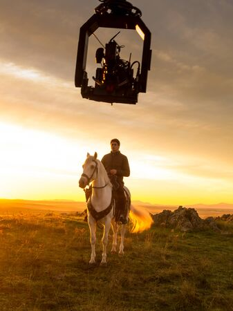 Actor riding a horse during the filming of a sequence for a television series.Crane camera shot at dawn. November 2016. Caceres. Spain.TV series: Still Star Crossed.