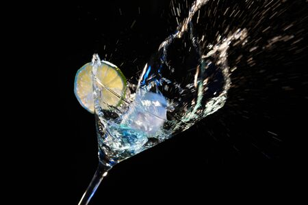 Refreshing drink served in cocktail glass, freezing splashing motion Фото со стока