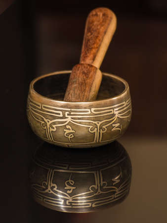 gong bowl: Tibetan bowl with its reflection and wood Stock Photo