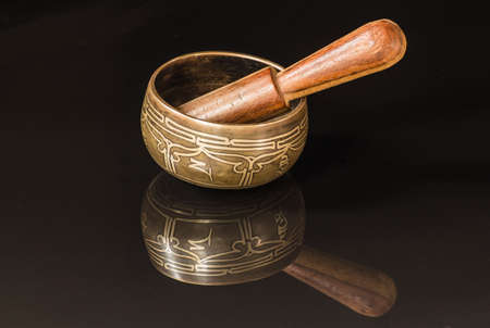 tantra: Tibetan bowl with  black reflaction and wood