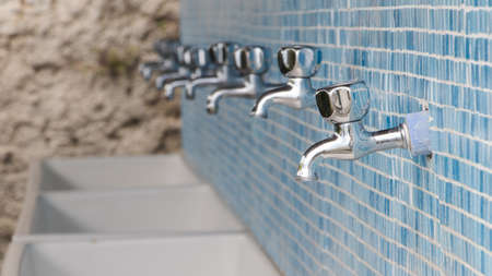 basins: taps and wash basins on blue tiles in camping
