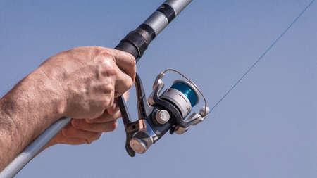 Fishing pole: hands rewinding a fishing pole reel Stock Photo