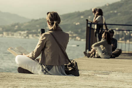 crosslegged: Sestri Levante, GE, Italy - May 30, 2015: a young woman reading a book  while looks at his phone on the port of Sestri Levante in a spring afternoon. She is sitting cross-legged wearing a shoulder bag in the background other people looking at the open sea Editorial