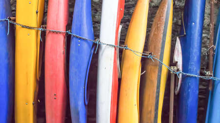 chaining: red, bue, yellow, white canoes in a row standing against the wall