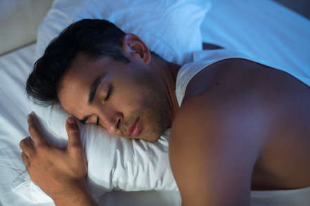 Close-up beautiful portrait of handsome man on the white bed. Archivio Fotografico