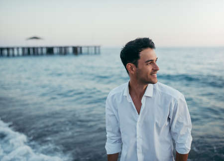 Handsome happy man wearing white shirt at the sea or the ocean background. Travel vacation holiday. Man walking at the sea, enjoy tropical season. Relax caucasian adult man looking away at sunset.. Banque d'images