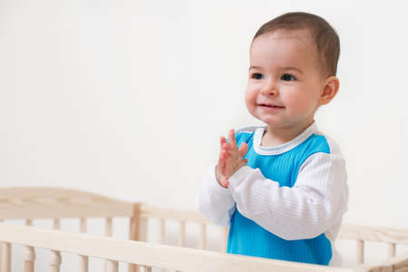 Smiling cute baby toddler look at one side in the bed on white background Фото со стока