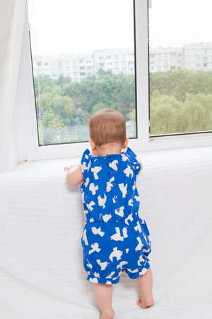 Beautiful baby standing next to window and look outside