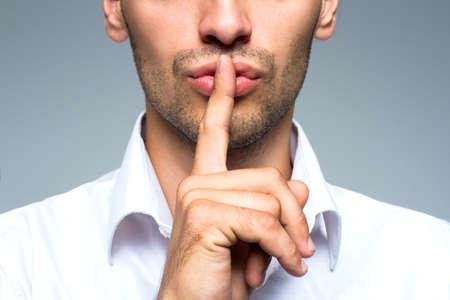 Businessman silent quiet gesture with finger Stockfoto