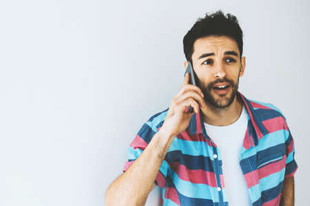 Portrait of Caucasian handsome man using and talking on mobile phone, troubled and surprised. Human emotions, expressions and attitude. Worry businessman using device for communication. Technology.