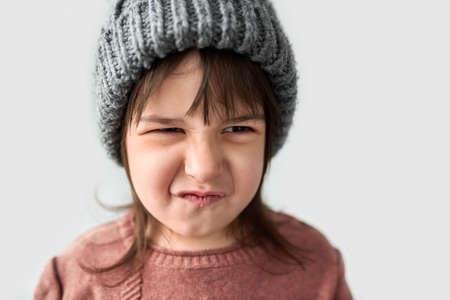 Studio closeup portrait of cute unhappy little girl with grumpy emotion in the winter warm gray hat, wearing sweater isolated on a white studio background.
