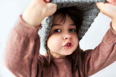 Cute Caucasian little girl playing peek-a-boo with the winter warm gray hat, wearing sweater isolated on a white studio background.