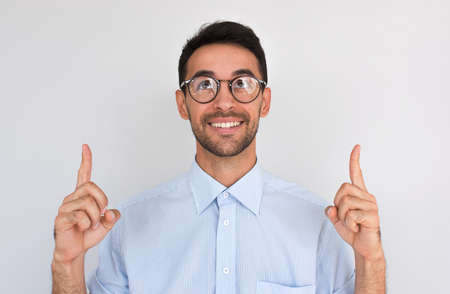 Horizontal closeup shot of happy satisfied Caucasian male points upwards with both index fingers, notices something amazing above head, looikng up, wearing round spectacles, against white studio wall