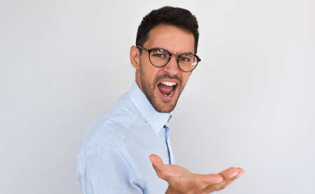 Portrait of angry young handsome male exclaims, feels furious while talking with someone, posing on white studio background. Caucasian man screams nervously, gesture with hand. Negative human emotion.