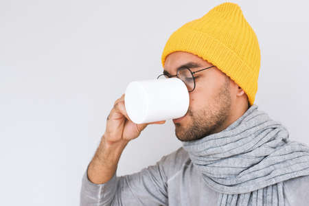 Side view of handsome male having sore throat influenza. Portrait of sick man have grippe and drinking cup of tea, wearing glasses, yellow hat, grey sweater and scarf. People, health, medicine concept