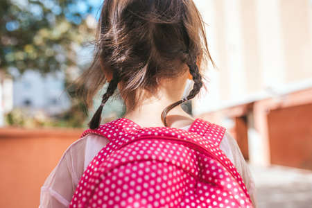 Closeup rear view portrait of cute little girl preschooler posing outdoor with pink backpack against blurred building. Happy kid toodler girl walking after learning school lessons. People, education 免版税图像
