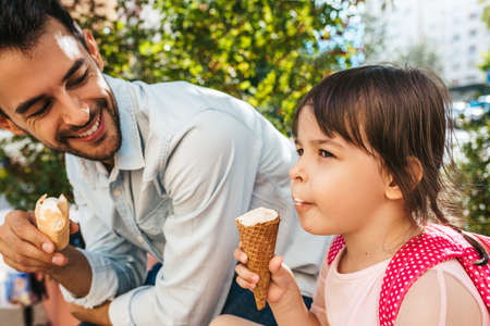 Closeup shot of happy cute little girl sitting with handsome dad on the city street and eating ice-cream outdoor. Fun girl kid and father have fun outside. Good relationship between dad and daughter