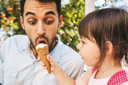 Closeup image of happy cute little girl sitting with handsome dad eating ice-cream outdoors. Fun girl kid and amazed father have fun and enjoy outside. Good relationship between dad and daughter.