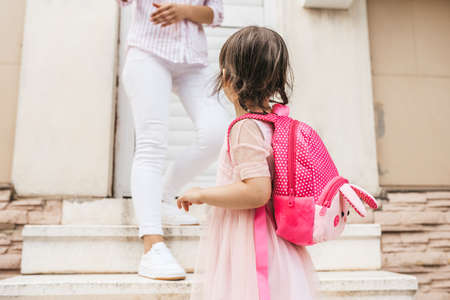 Image of mother standing on the stairs against the home saying goodbye to her daughter as she leave for kindergarten. Cute little girl wears dress and backpack going to preschool, waving to mother Zdjęcie Seryjne
