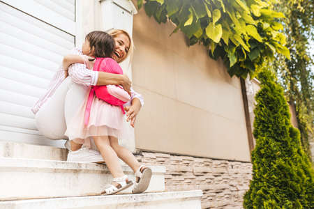 Horizontal image of happy mother with meets her pupil daughter going back at home from kindergarten. Cute little girl with mom embrace each other, feeling happy after the first preschool day. Family