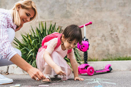 Happy cute little girl wears dress and mother drawing with colorful chalks on the sidewalk. Caucasian female play together with kid preschooler with backpack outdoor. Mom and child activity outside