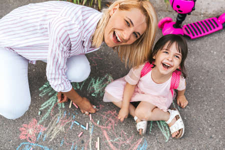 Happy smiling little girl and mother laughing and drawing with chalks on the sidewalk. Caucasian female play together with her cute kid preschooler with backpack outdoor. Mom and child activity