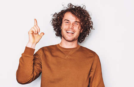 Confident young male wears brown pullover indicates up with fore finger, smiling and looking at the camera, demonstrates something at blank copy space for advertisement. People and emotion concept
