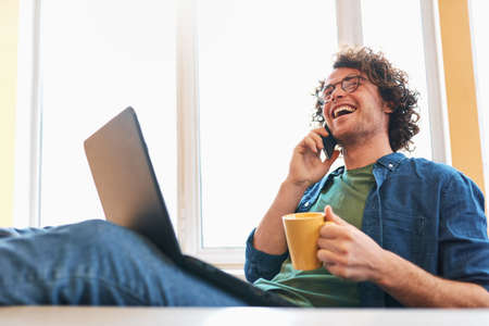 Young freelancer man sitting in the home office talking on mobile phone while working on a laptop. Smiling businessman working on laptop, speaking on cellphone and drinking a coffee.