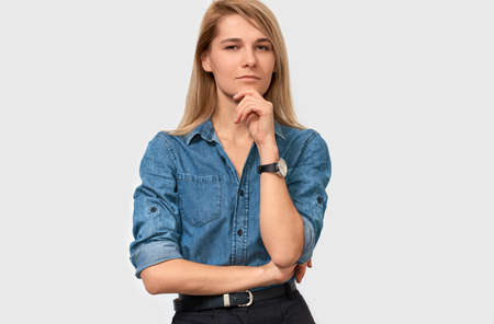 Serious pretty blonde young woman wearing denim shirt with finger folded on the chin frowning her face and looking to the camera on white studio background. Thoughtful female thinking about something.
