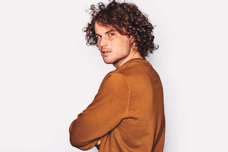 Rear view studio shot of serious male, looks directly at the camera, wears brown pullover, isolated over white background. Portrait of businessman freelancer with curly hair. Negative emotion, people