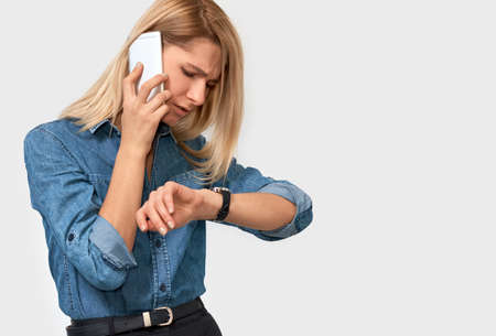 Horizontal closeup portrait of frustrated young blonde woman talking on mobile phone, looking at the watch, because her colleague is late at the meeting. Young businesswoman working with gadget online