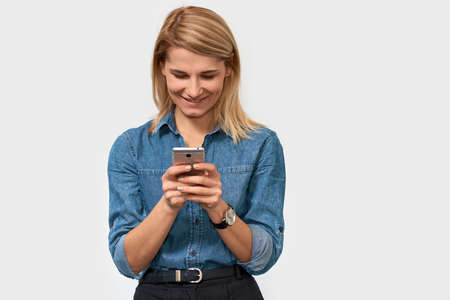 Horizontal image of joyful blonde woman, texting message on smart phone, feeling happy to reading good news, wears denim shirt, poses on white studio background with copy space for your promotion Banque d'images - 117460748