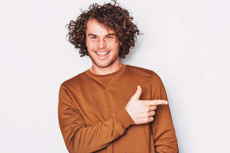 Happy young male with curly hair wears pullover indicates a side with fore finger, smiling and looking at the camera, demonstrates something at blank copy space for promotion. People, emotion concept Banco de Imagens