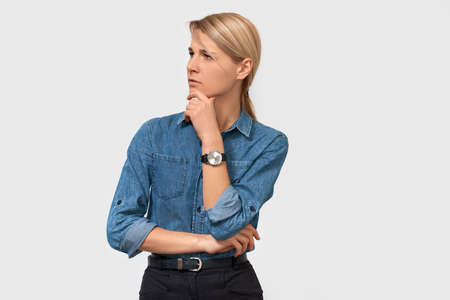 Mistrustful pensive young business woman in denim shirt with finger touching her chin and looking to the one side over white studio background. Thoughtful female thinking about something.