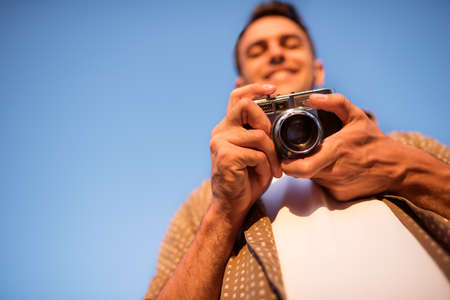 Bottom view of smiling handsome young man with vintage camera, take a picture on sky background. Autumn. Summer. Mood background. Photography. Foto de archivo